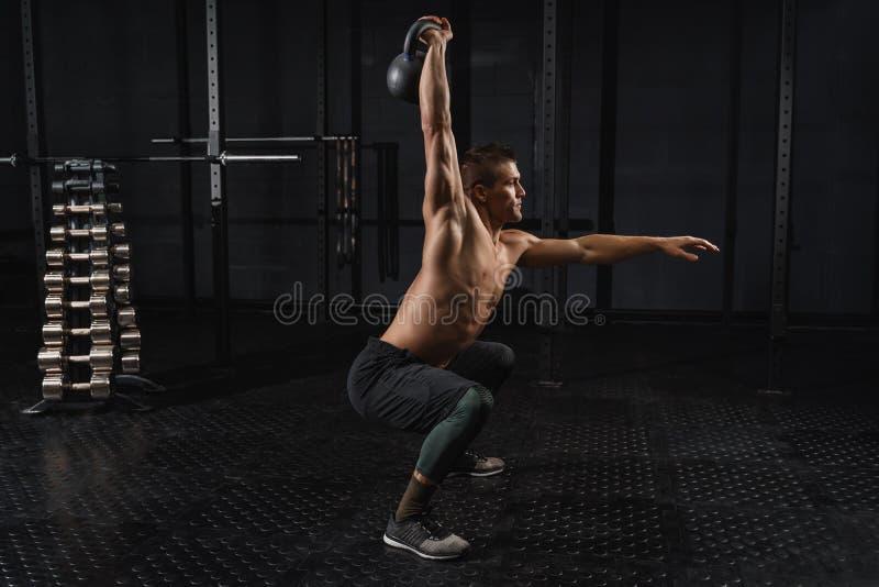 Exercício do homem do exercício do balanço de Kettlebells no gym Treinamento de CrossFit fotos de stock royalty free