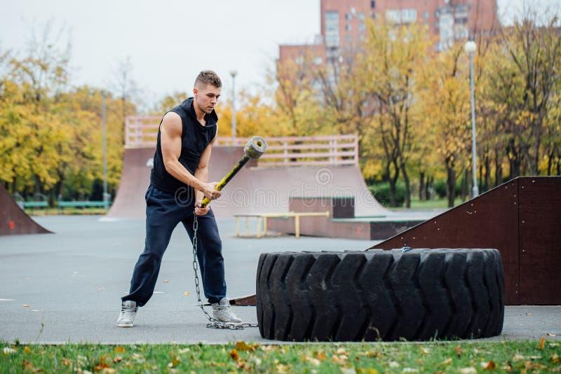 Exercício do homem do esporte da aptidão exterior com o pneu do martelo e do trator imagens de stock royalty free