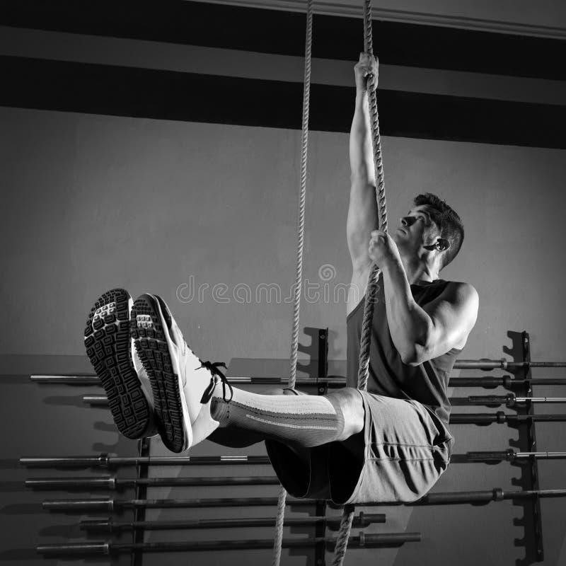 Exercício do homem do exercício da escalada da corda no gym fotos de stock royalty free