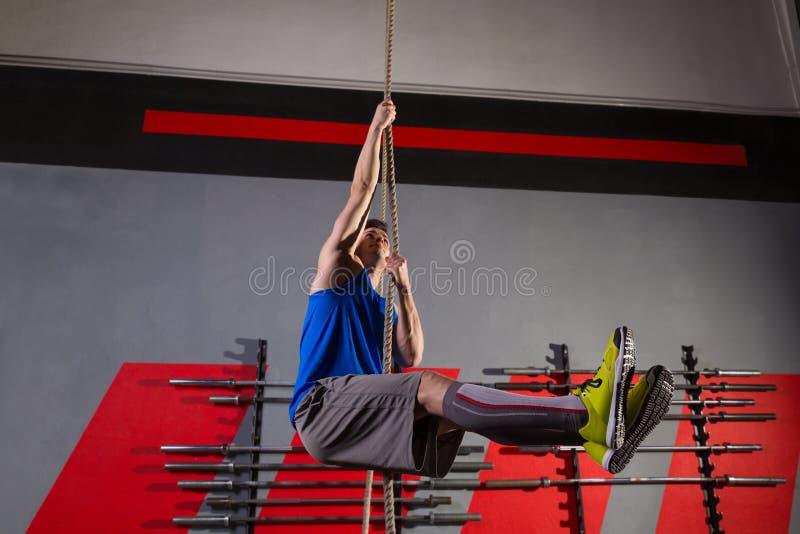Exercício do homem do exercício da escalada da corda no gym fotos de stock