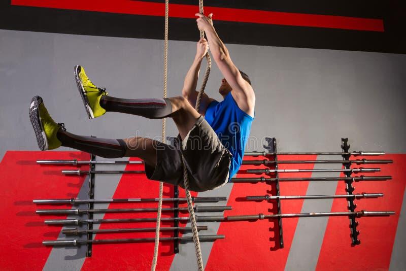 Exercício do homem do exercício da escalada da corda no gym imagens de stock royalty free