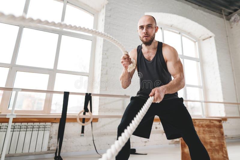 Exercício do homem forte com cordas da batalha no gym claro fotos de stock