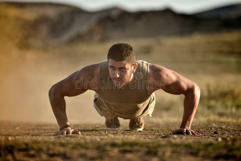 Exercício do homem novo exterior no campo empoeirado fotografia de stock royalty free