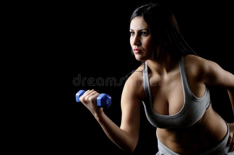 Exercício do peso da mulher do Dumbbell na ginástica fotos de stock