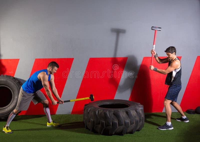 Exercício dos homens de batidas do pneu do malho no gym imagem de stock royalty free