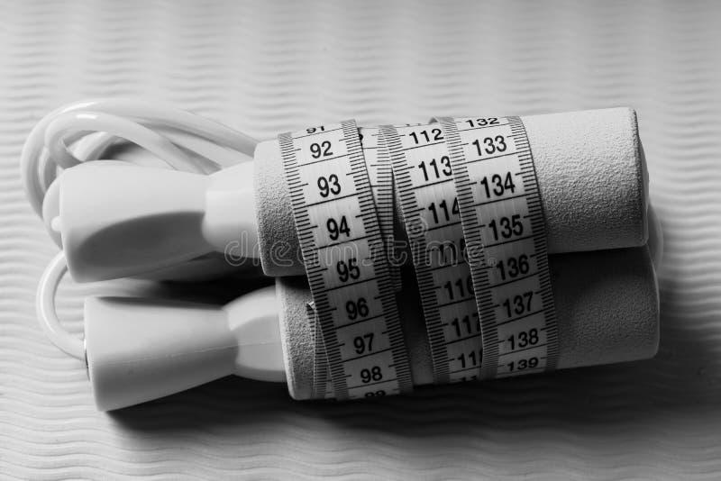 Exercício e conceito do treinamento Corda de salto na cor ciana amarrada com fita de medição fotografia de stock royalty free