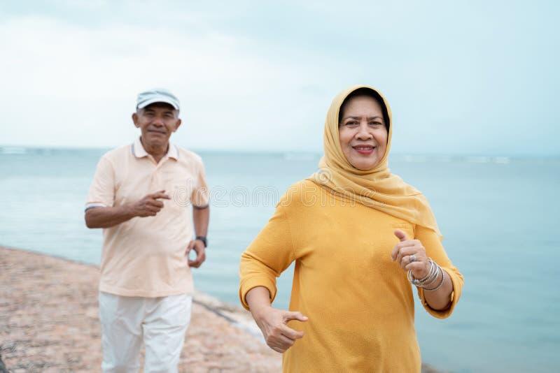 Exercício e corredor velhos muçulmanos dos pares na praia imagens de stock