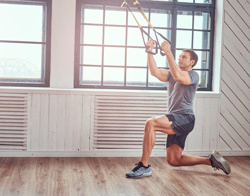 Exercício fazendo masculino da aptidão muscular com TRX Exercício funcional em casa com laços de TRX foto de stock