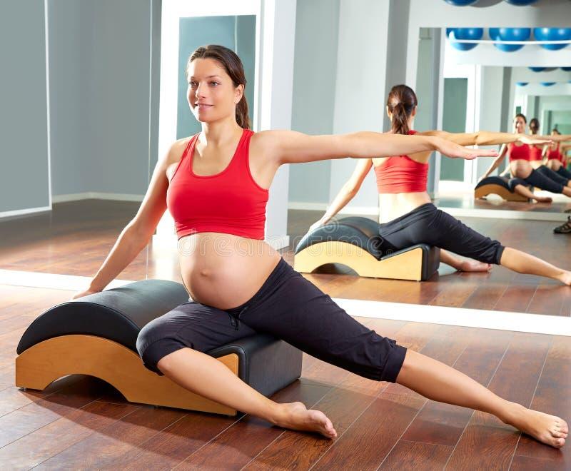 Exercício lateral dos stretchs dos pilates da mulher gravida fotografia de stock