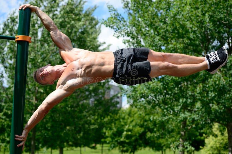 Exercício muscular da rua da prática do homem em um gym exterior fotografia de stock