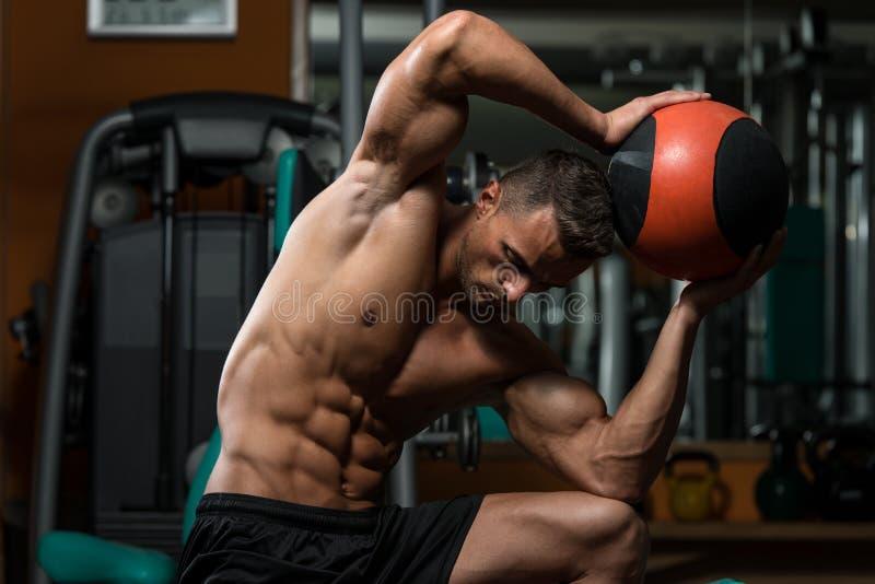Exercício muscular do homem com bola médica fotos de stock