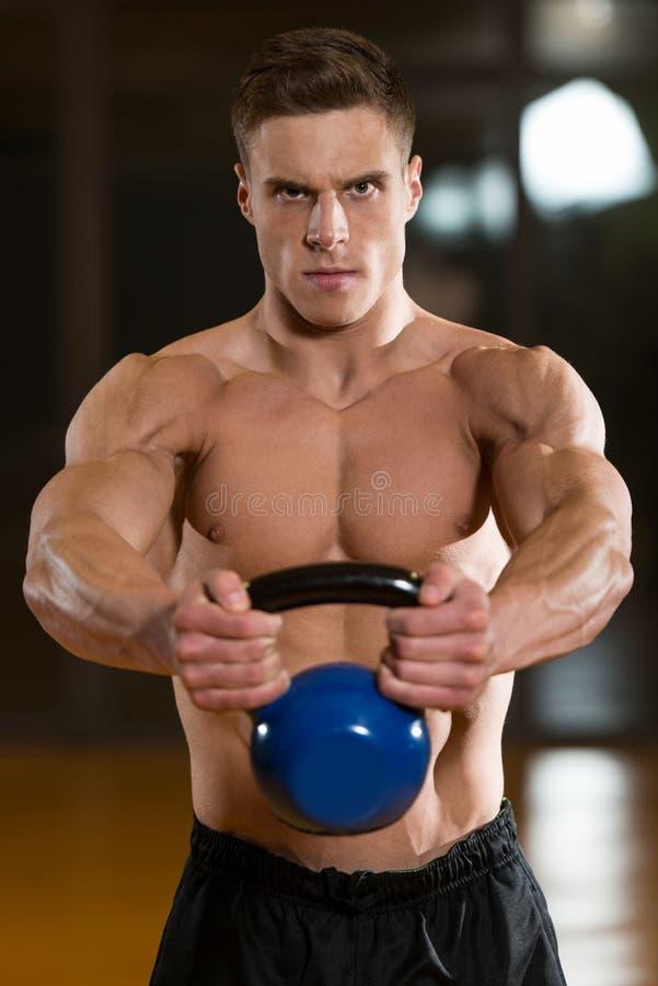 Exercício muscular do homem com KettleBell foto de stock royalty free
