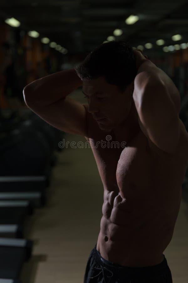 Exercício muscular do homem com pesos na sala escura foto de stock royalty free