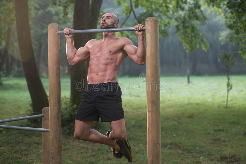 Exercício muscular do homem em barras no Gym exterior foto de stock