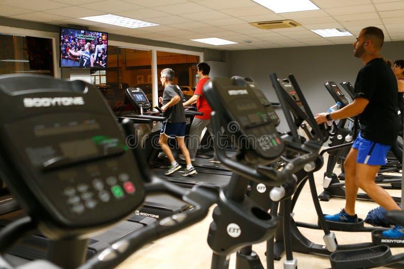 Exercício na opinião lateral das máquinas da aptidão do gym imagens de stock royalty free