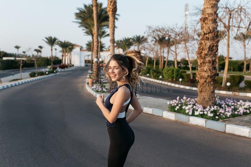 Exercício na rua com as palmeiras da jovem mulher atrativa no sportwear que sorri à câmera Expressando o posititvity, verdadeiro fotografia de stock royalty free