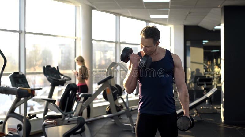 exercício no gym, peso de levantamento do halterofilista muscular, fazendo ondas do peso imagem de stock royalty free