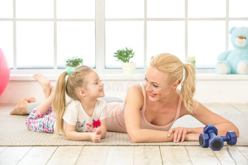 Exercício novo da mãe e da filha junto dentro imagens de stock royalty free