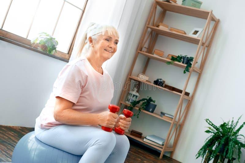 Exercício superior da mulher em casa que senta-se na bola do exercício que guarda pesos fotografia de stock