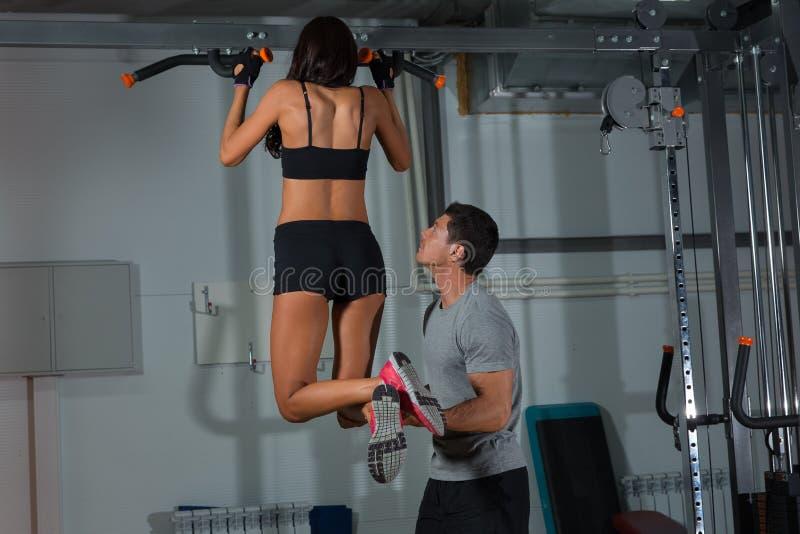 Exercícios da mulher na barra horizontal com instrutor fotografia de stock