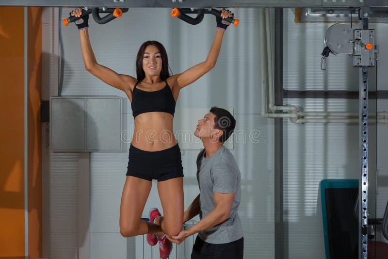 Exercícios da mulher na barra horizontal com instrutor foto de stock royalty free