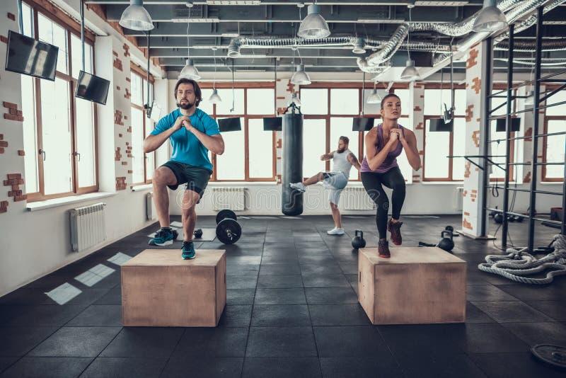 Exercícios do grupo de Crossfit Guy With Punching Bag imagem de stock