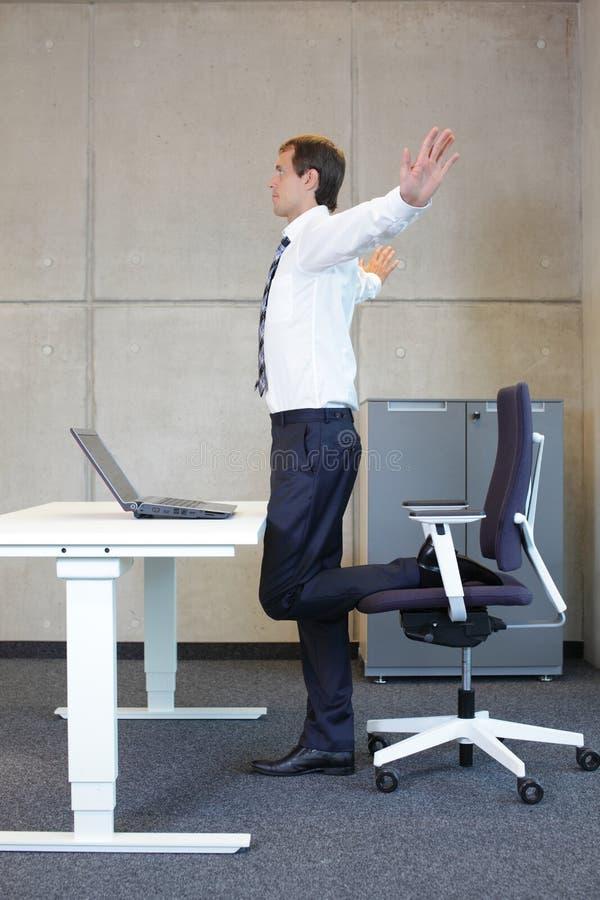 Exercícios do homem de negócio no escritório foto de stock
