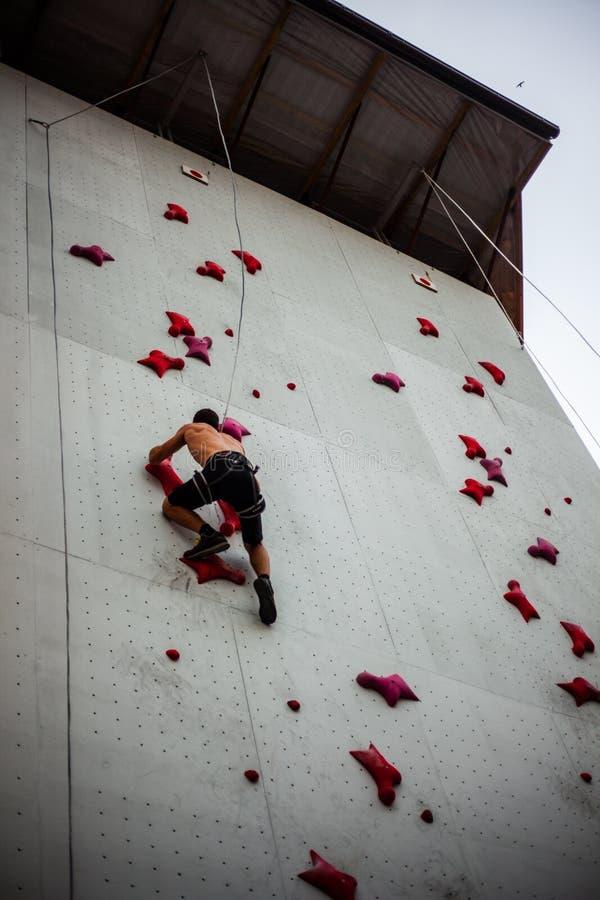 Exercícios do homem no montanhista de rocha interno imagem de stock royalty free