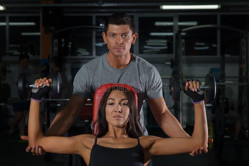 Exercícios dos pares com pesos junto no gym imagem de stock