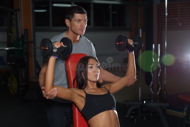 Exercícios dos pares com pesos junto no gym foto de stock royalty free