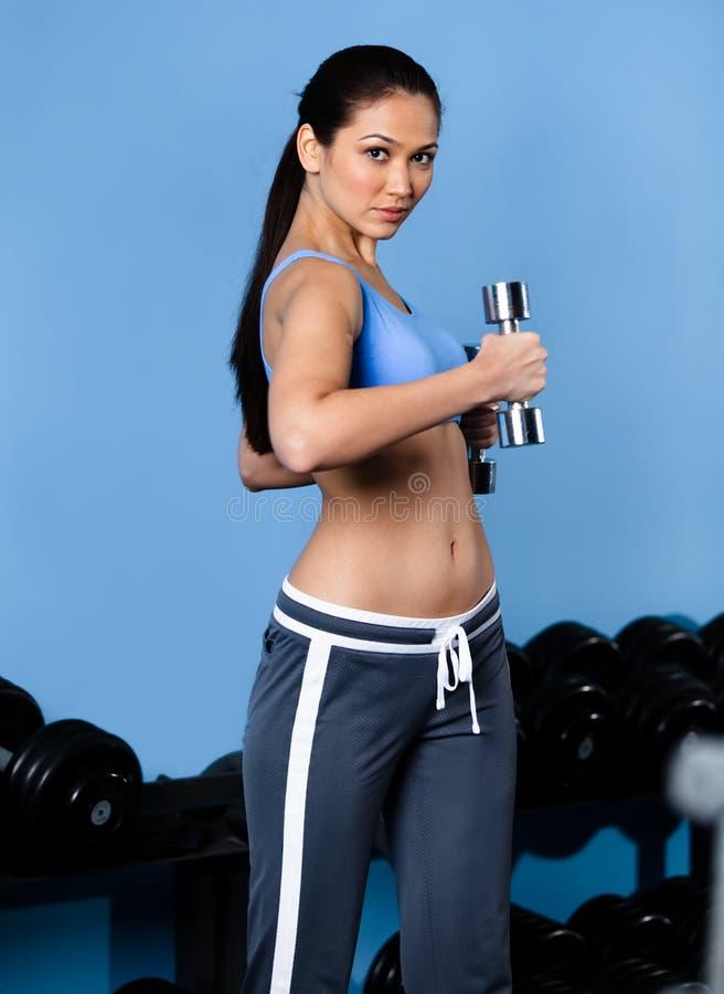 Exercícios Sportive da mulher com dumbbells foto de stock royalty free