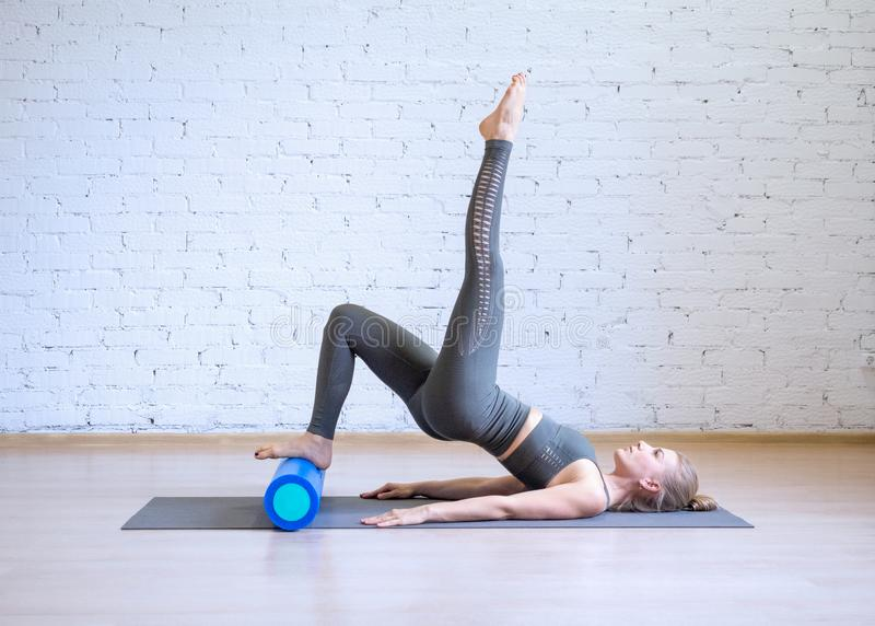 Exerc?cio de Pilates Mulher no terno cinzento dos esportes que faz o exerc?cio na matem?tica com rolo da aptid?o, fundo do estilo imagens de stock