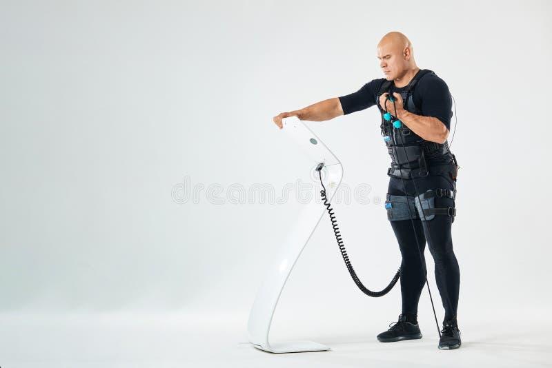 Exercice actif fort d'homme avec le costume et l'exxpander de stimulation de SME image stock