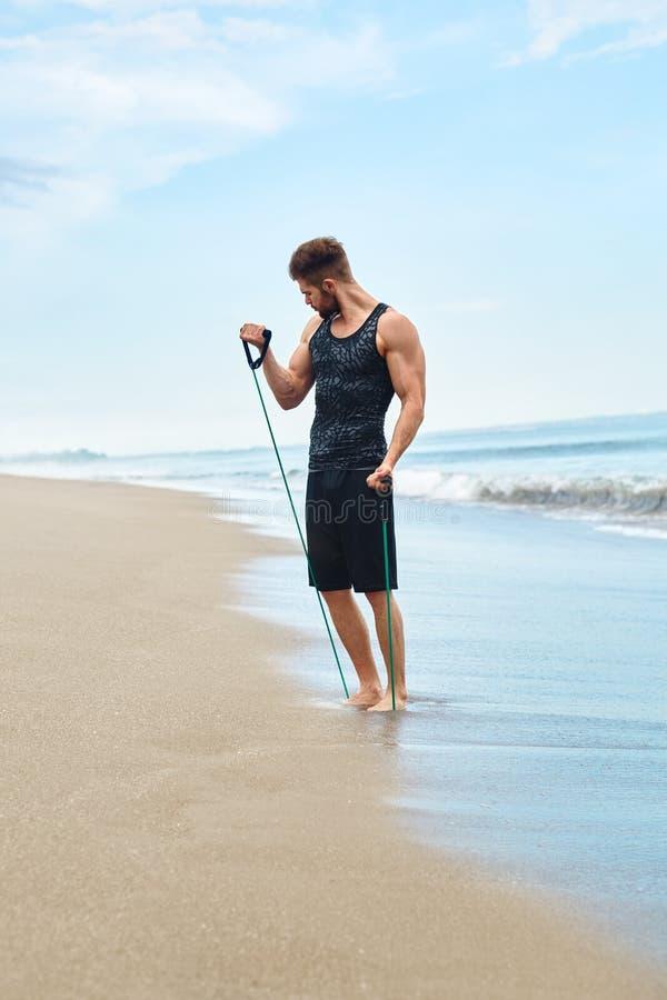 Exercice d'homme extérieur, faisant l'exercice de séance d'entraînement à la plage Forme physique image stock