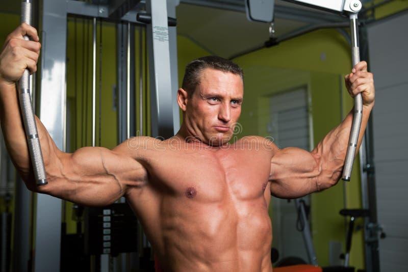 Exercice d'homme formé par muscle sur le club de forme physique images libres de droits