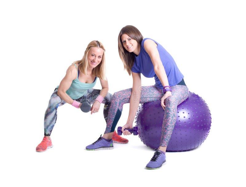 Exercice de femme de deux sports avec une boule et des haltères de pilates images stock