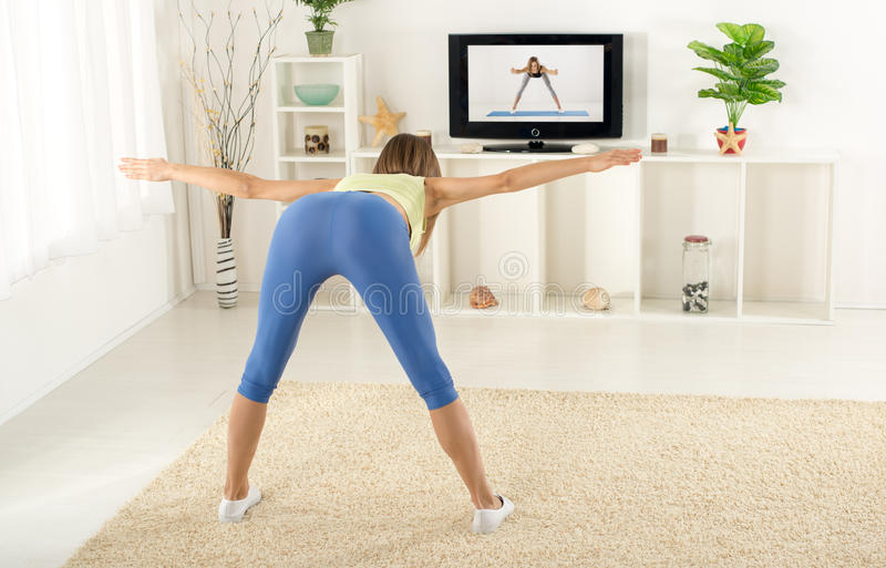 Exercice de femme en Front Of TV photos stock
