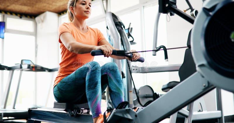 Exercice de formation croisée de femme de séance d'entraînement cardio- utilisant la machine à ramer photographie stock libre de droits