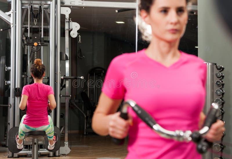 Exercice de jeune femme son de retour et bras dans le gymnase photos stock
