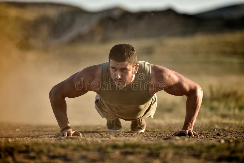 Exercice de jeune homme extérieur sur le champ poussiéreux photographie stock libre de droits