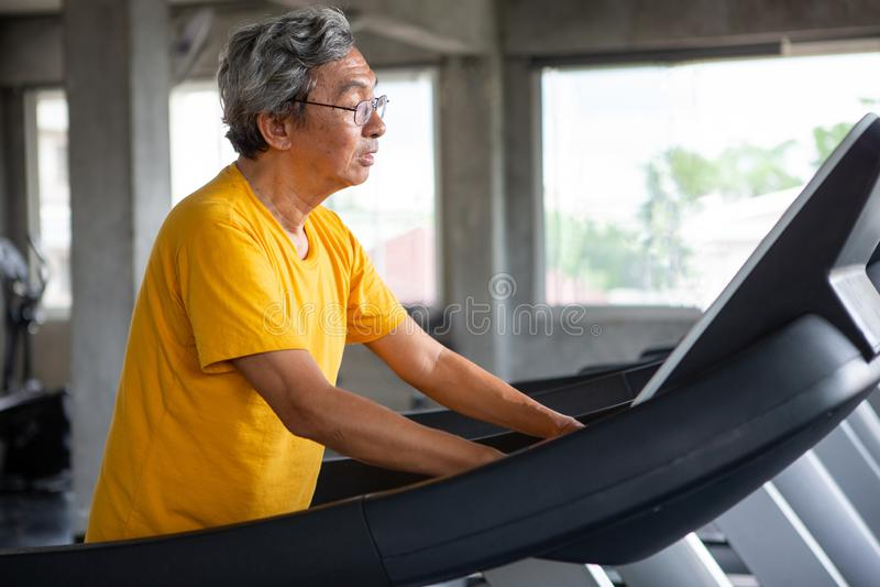 exercice de marche asiatique d'homme supérieur sur la séance d'entraînement de tapis roulant dans le gymnase de forme physique sp image stock