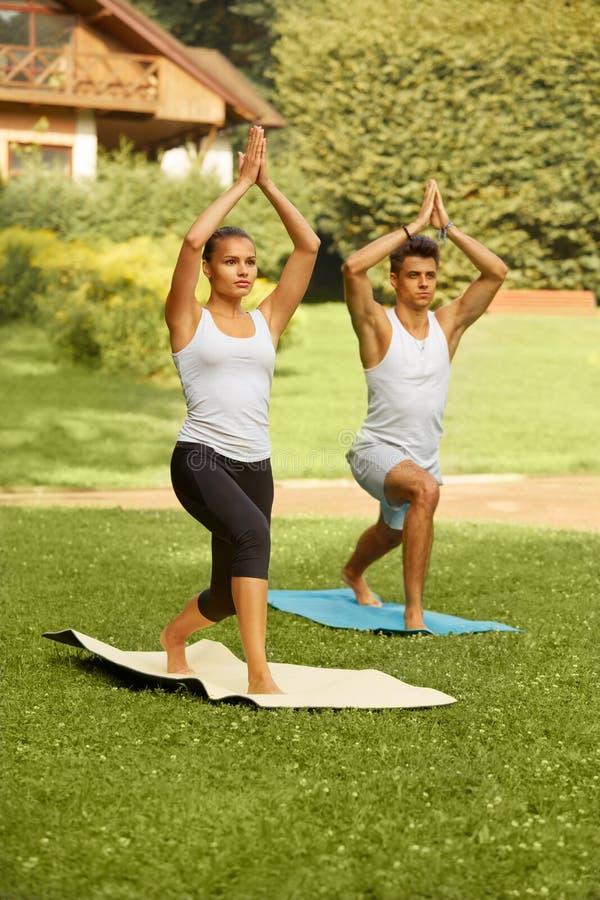 Exercice de yoga Jeunes couples méditant dans le centre de fitness images stock