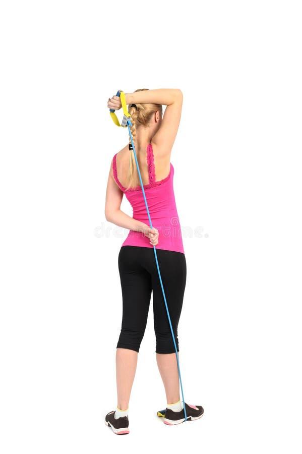Exercice femelle d'extension de triceps utilisant la bande en caoutchouc de résistance image stock