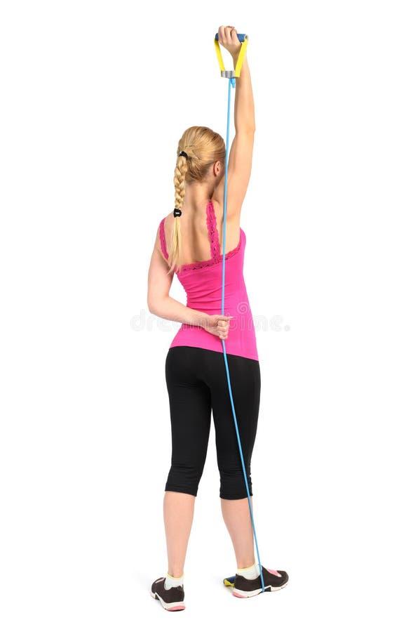 Exercice femelle d'extension de triceps utilisant la bande en caoutchouc de résistance photographie stock