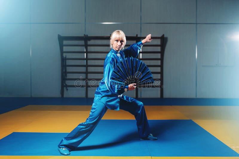 Exercice femelle de maître de wushu avec la fan, art martial image stock