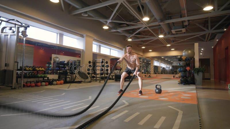 Exercice musculaire de séance d'entraînement de formation d'homme avec des cordes dans le centre de fitness images libres de droits
