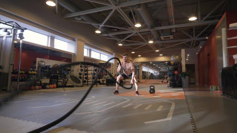 Exercice musculaire de séance d'entraînement de formation d'homme avec des cordes dans le centre de fitness images stock
