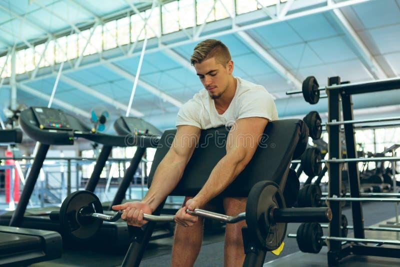 Exercice sportif masculin avec le barbell sur le banc de prédicateur au centre de fitness images stock