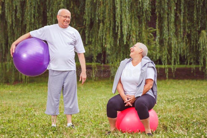 Exercice supérieur - couple supérieur heureux se reposant sur des boules de forme physique en parc images libres de droits