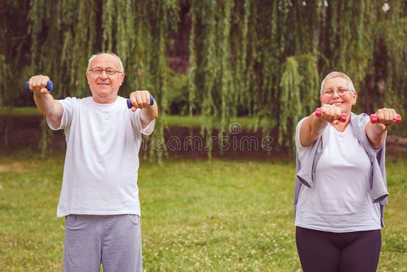Exercice supérieur - exercice de sourire de forme physique de pratique en matière d'homme supérieur et de femme avec des haltères images libres de droits